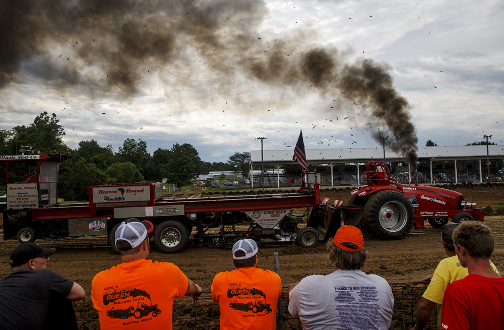 Dirt clods and a plume of smoke trail behind Bill Painter's tractor as he competes during the tractor pull at the Montgomery County Fair in Butler Sunday, June 28, 2015. Ted Schurter/The State Journal-Register