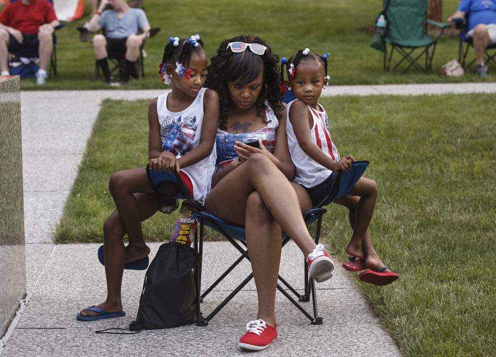 Ellistina Parker shares a chair with her daughters Dariyah Prince, left, and Eloni Jones as they wait for the fireworks on the lawn of the Capitol Saturday, July 4, 2015. Ted Schurter/The State Journal-Register