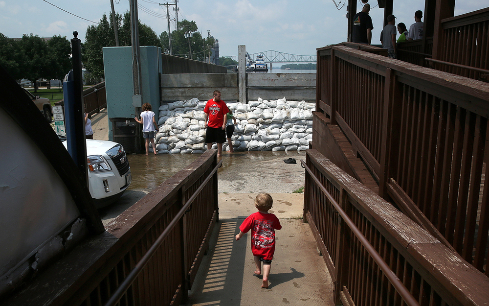Adyen Green of Beardstown runs toward a small wall of sandbags set up near the base of the river overlook Wednesday July 1, 2015 in Beardstown, Ill. Adyen and his siblings, Alexandra Dunn and Kayda Nava, were playing in water that had seeped under the sandbags. David Spencer/The State Journal-Register
