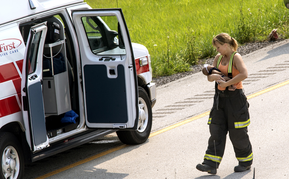 Dawson Fire Protection District firefighter Laura Constant carries an infant to an ambulance at the scene of a multiple injury rollover accident in the westbound lanes of Interstate 72 near Buffalo Saturday, July 4, 2015. The westbound lanes were closed for several hours for accident reconstruction. Ted Schurter/The State Journal-Register
