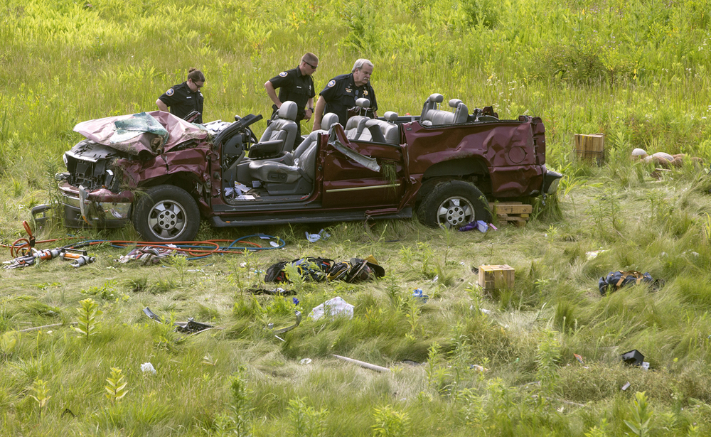 Police officials look at the SUV involved in a rollover accident on Interstate 72 near Buffalo Saturday, July 4, 2015. Ted Schurter/The State Journal-Register