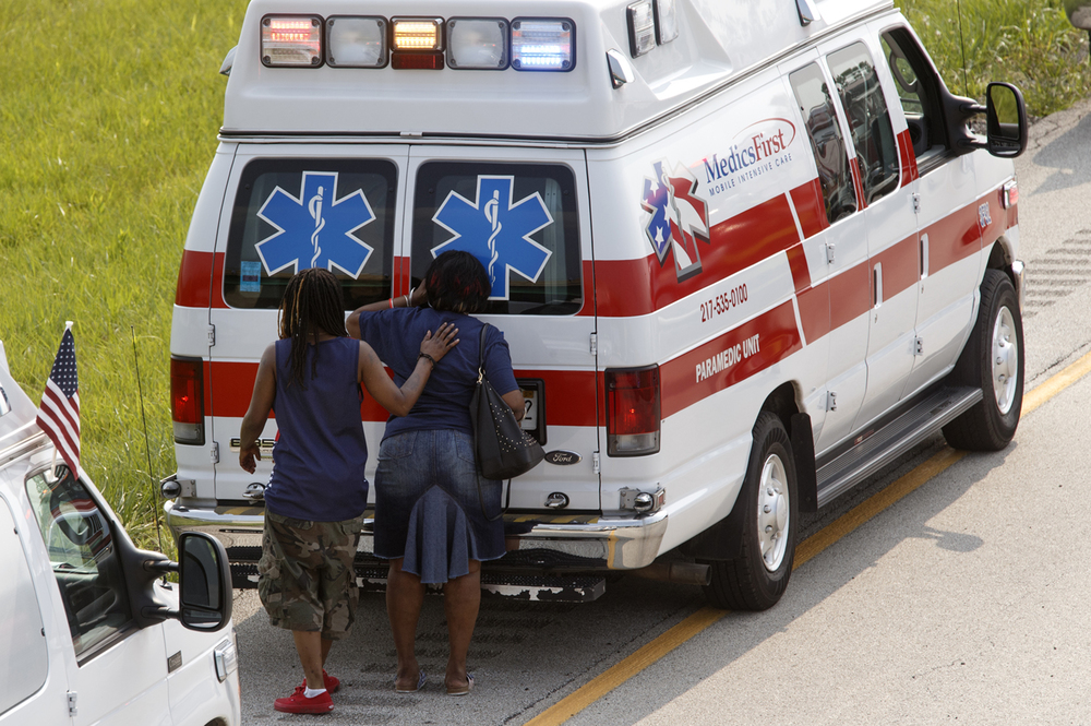 A woman peers into the back of an ambulance after an infant was loaded at the scene of an SUV rollover accident on Interstate 72 near Buffalo Saturday, July 4, 2015. Ted Schurter/The State Journal-Register