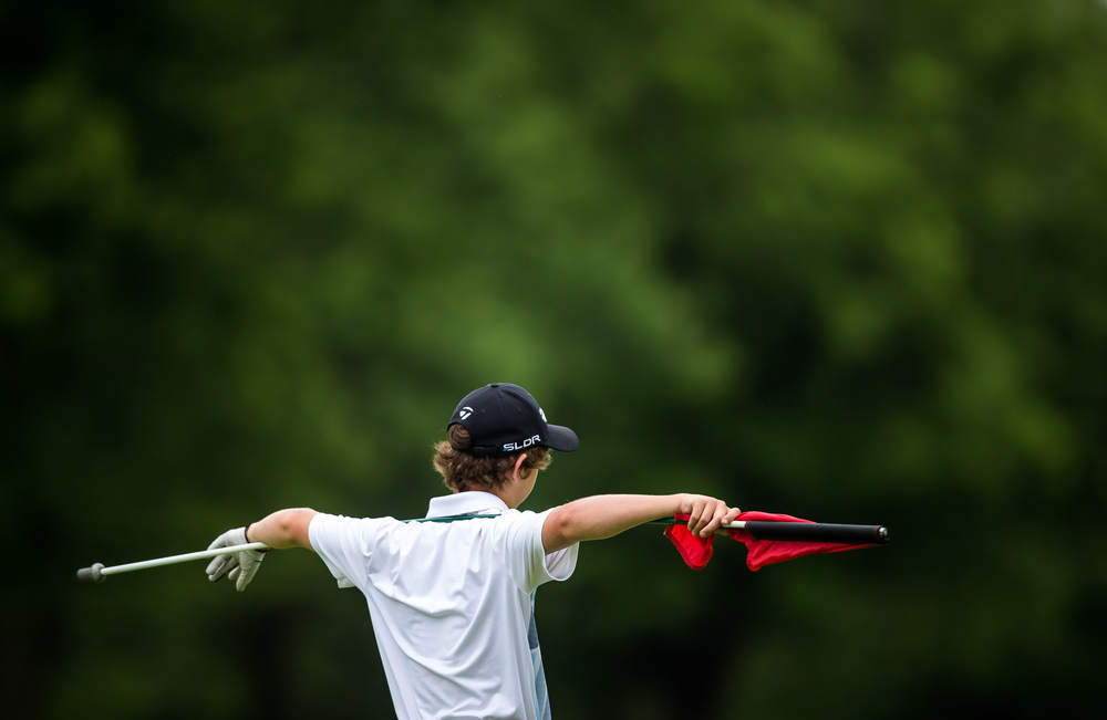 Benjamin Rademaker waits with the flag as his playing partners finish putting out on the No. 15 hole during the Drysdale Junior Golf Tournament at Lincoln Greens Golf Course, Tuesday, July 7, 2015, in Springfield, Ill. Justin L. Fowler/The State Journal-Register