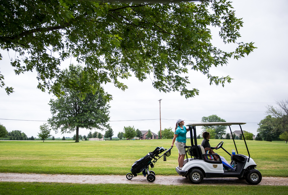 Ali Hurley hitches a ride on a golf cart after her match ended during the Drysdale Junior Golf Tournament at Lincoln Greens Golf Course, Tuesday, July 7, 2015, in Springfield, Ill. Justin L. Fowler/The State Journal-Register