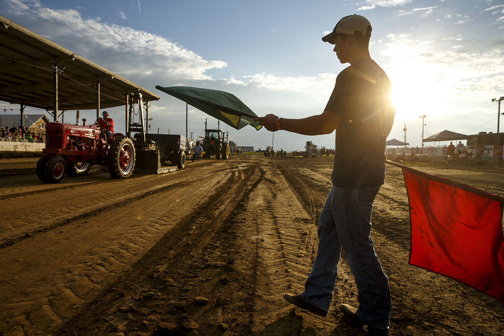 Flagman R.J. Ruppel  monitors a contestant's forward progress at the tractor pull during the Menard County Fair Wednesday, July 15, 2015. The tractor pull resumes Saturday; the fair continues through July 19th. Ted Schurter/The State Journal-Register