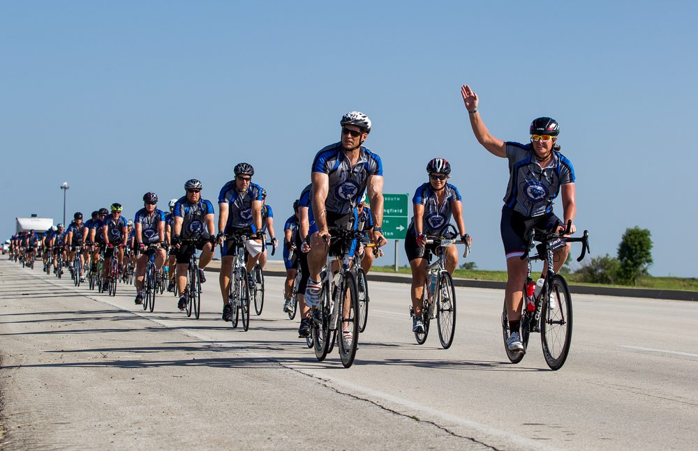 "Illinois State Police Sgt. Kim Cessna, right, waves as she leads the pack of riders after crossing the Stuttle Road overpass over Interstate 55 in Williamsville during the Illinois Chapter of Concerns of Police Survivors,  C.O.P.S., 11th annual Cycle Across Illinois , Friday, July 17, 2015, in Williamsville, Ill. The Stuttle Road overpass over Interstate 55 in Williamsville was renamed  ""Trooper Bernard D. Skeeters Memorial Overpass"" to honor the trooper killed when his patrol car was struck from behind by a tractor trailer on I-55 in 1982. Justin L. Fowler/The State Journal-Register"