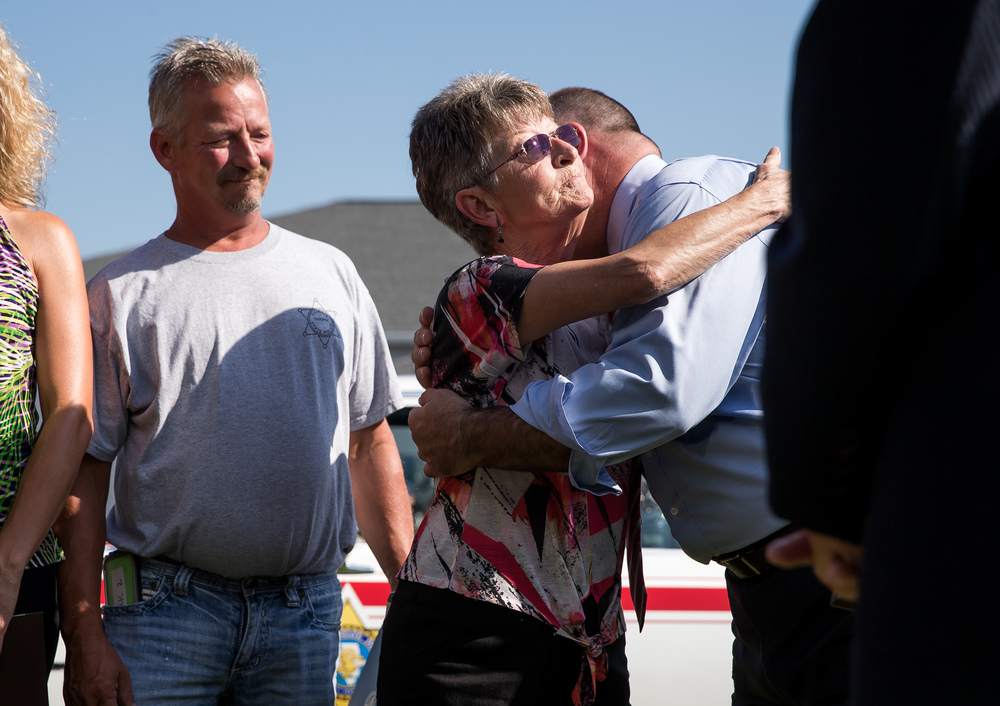 "Marie Cook, the widow of Trooper Bernard D. Skeeters, gets a hug from State Sen. Sam McCann during a memorial ceremony to honor Skeeters and rename the Stuttle Road overpass over Interstate 55 in Williamsville in his honor, Friday, July 17, 2015, in Williamsville, Ill. The Stuttle Road overpass was renamed the ""Trooper Bernard D. Skeeters Memorial Overpass"" to honor the trooper killed when his patrol car was struck from behind by a tractor trailer on I-55 in 1982. Justin L. Fowler/The State Journal-Register"
