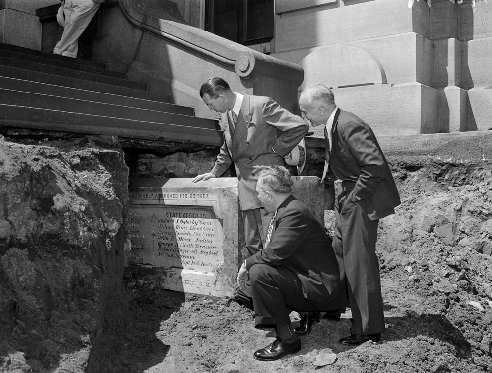 Sen. Arnold Benson, Republican candidate for Secretary of State, Richard Yates Rowe, Illinois Secretary of State and Paul Angle, state historian view the original cornerstone at state Capitol uncovered, July 17, 1944. File/The State Journal-Register