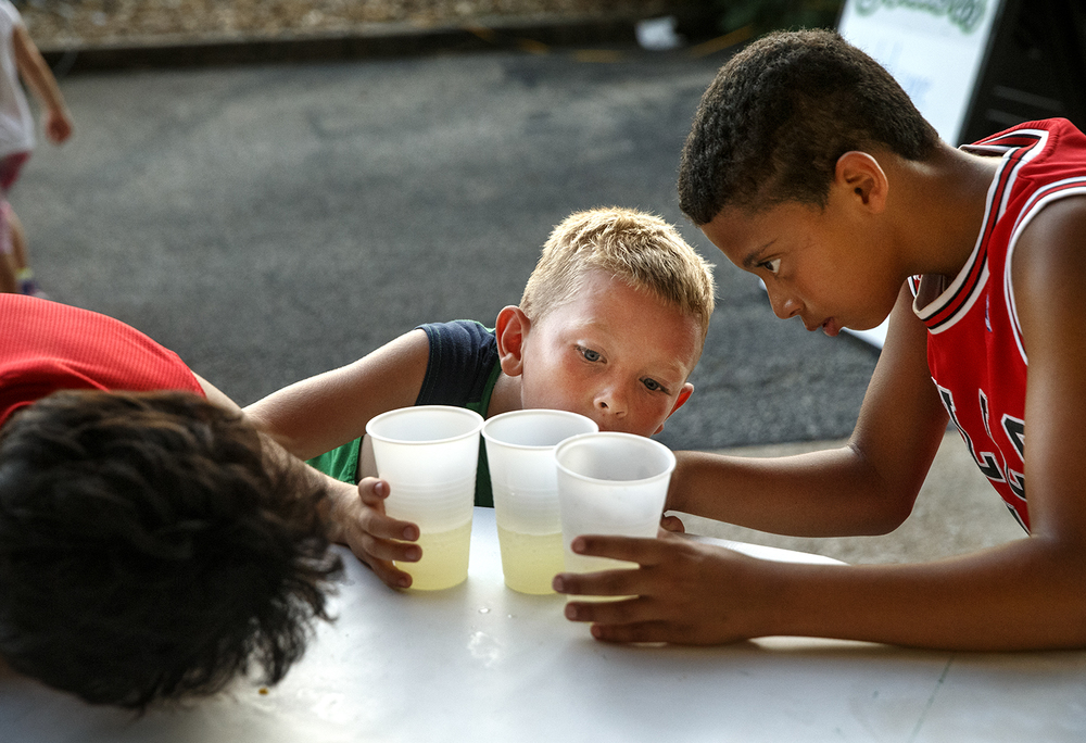 Dreon Dea, his cousin Kyler Dea and Devin Neal carefully examine whether the lemonade they just divided into three parts is equal as they seek relief from the triple-digit heat index at the Springfield Sliders game Friday, July 17, 2015. Ted Schurter/The State Journal-Register