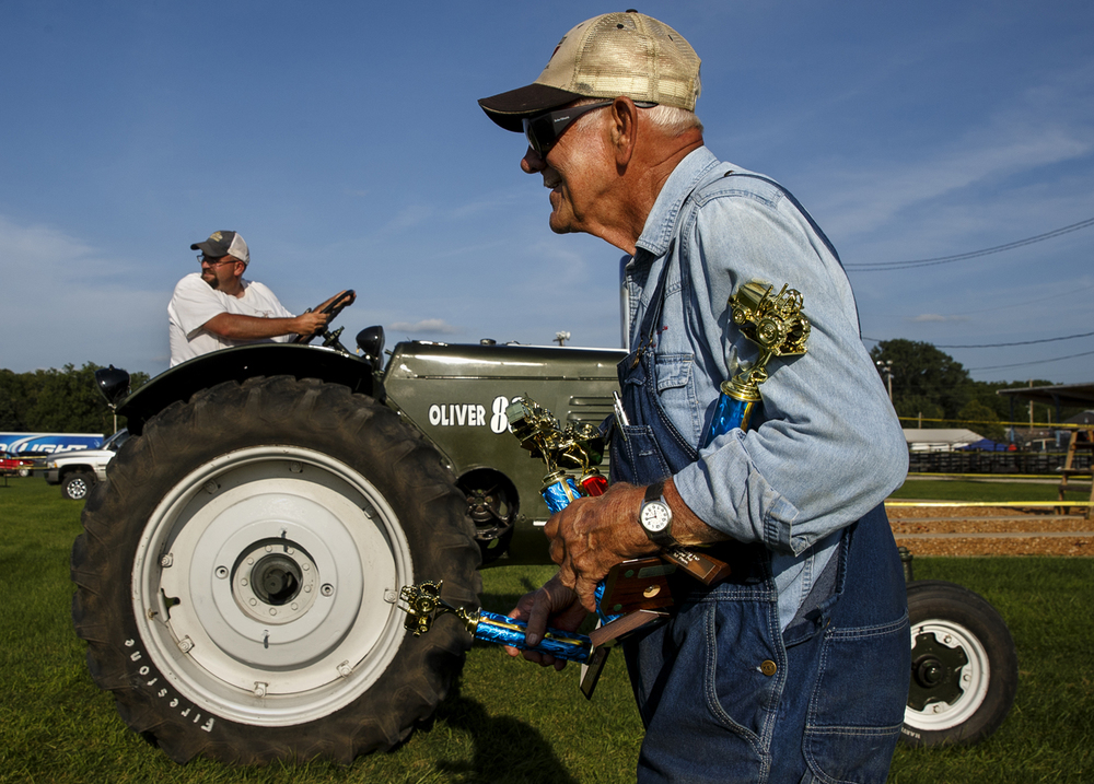 Duane Schleder of Pekin, Ill., carries home three first place trophies and one second place trophy after competing in the antique tractor pull during the Menard County Fair Wednesday, July 15, 2015. Ted Schurter/The State Journal-Register
