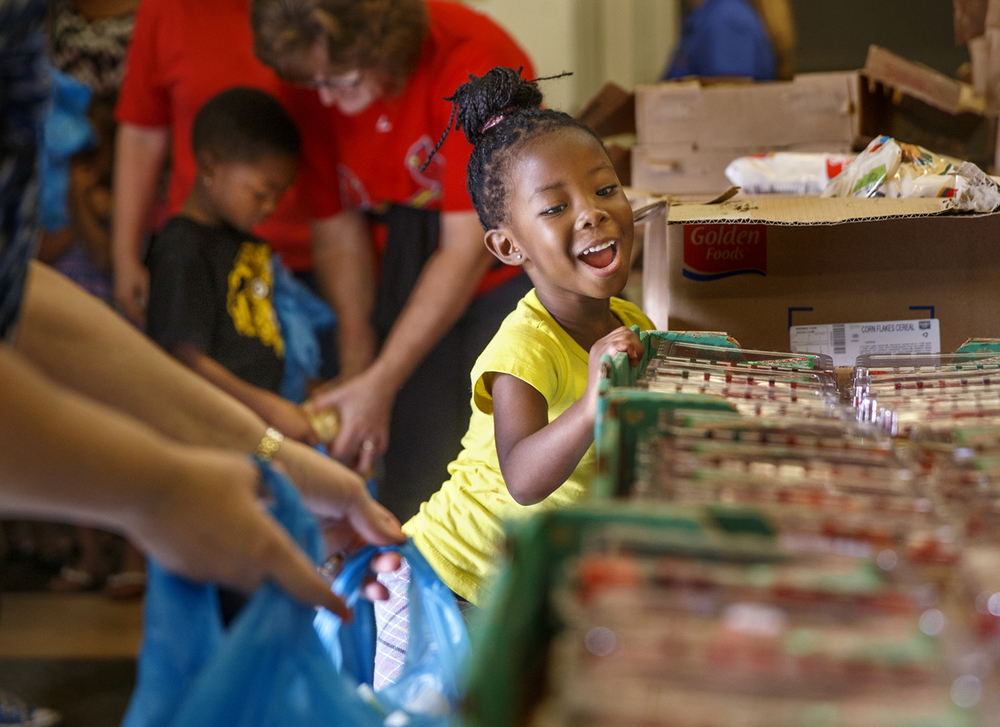 Kaylin Brown excitedly eyes the boxes of strawberries available to students at St. Patrick Catholic School from the Central Illinois Foodbank mobile pantry Thursday, July 16, 2015. Roughly 40 students filled grocery bags with fruit, cereal and other assorted food items as well as potatoes and a watermelon. The mobile food pantry will be stopping at five more schools this summer. Ted Schurter/The State Journal-Register