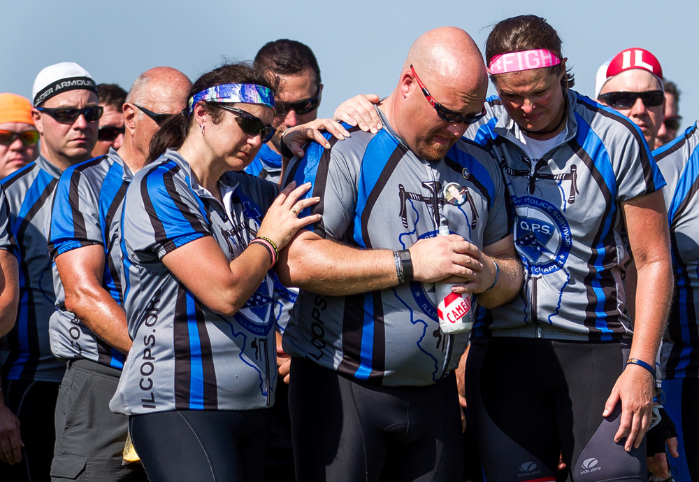 C.O.P.S. riders Kenny Deatherage, center, the brother of trooper Kyle Deatherage killed in 2012, is hugged by, Shelly Kellums, left, the sister of Sgt. Rodney Miller who was killed in 2006, and Illinois State Police Sgt. Kim Cessna, right, as the bagpipes are played during a ceremony for Trooper Bernard D. Skeeters, Friday, July 17, 2015, in Williamsville, Ill. The Illinois Chapter of Concerns of Police Survivors,  C.O.P.S., are cycling from Alton to Chicago during the 11th annual Cycle Across Illinois to honor and celebrate the lives of fallen officers and support their families. Justin L. Fowler/The State Journal-Register
