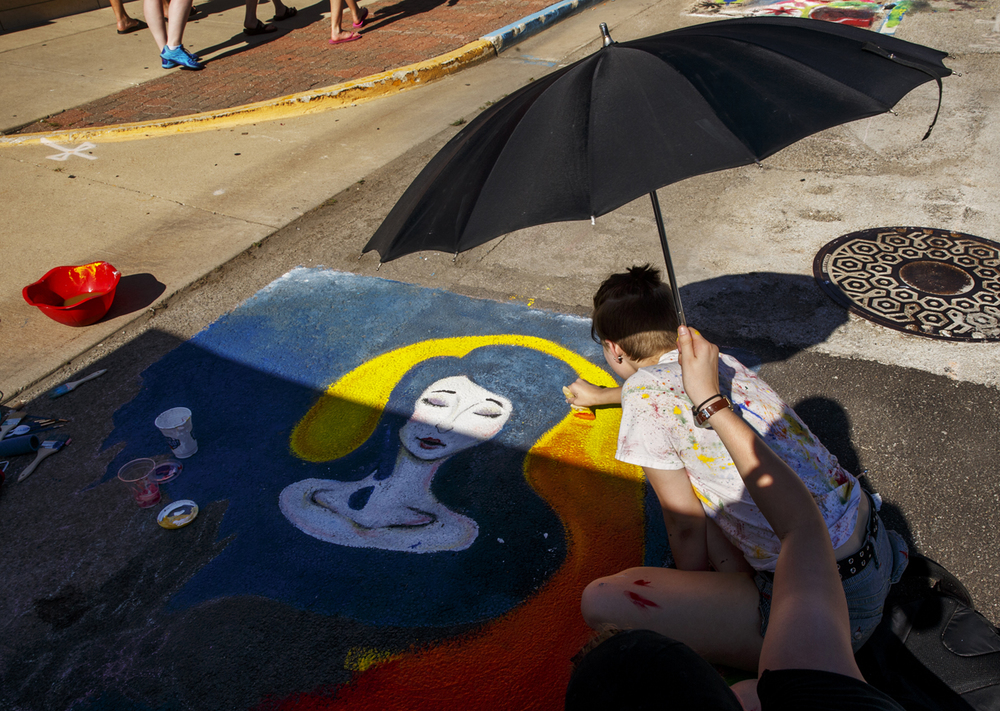 Brianna Skeels works under the shade of an umbrella held by Nichole Taylor during the third annual Paint the Street event in downtown Springfield Saturday, July 18, 2015. Ted Schurter/The State Journal-Register