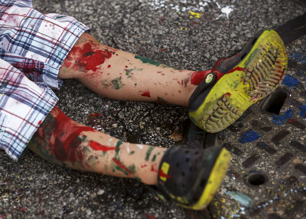 Noah Cyphers' legs were well painted after an hour of painting during the third annual Paint the Street event in downtown Springfield Saturday, July 18, 2015. Ted Schurter/The State Journal-Register