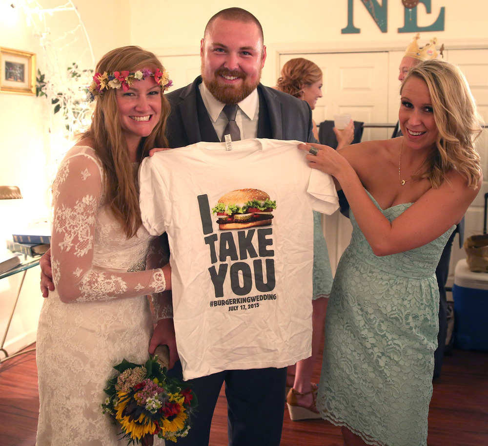 Newlyweds Joel Burger and Ashley King, and bridesmaid Jackie Yates, show off a t-shirt provided by the Burger King restaurant chain during the couple's wedding reception Friday, July 17, 2015 in Jacksonville, Ill. The shirt and other promotional items were supplied by the company, which also picked up the tab for the reception. David Spencer/The State Journal-Register
