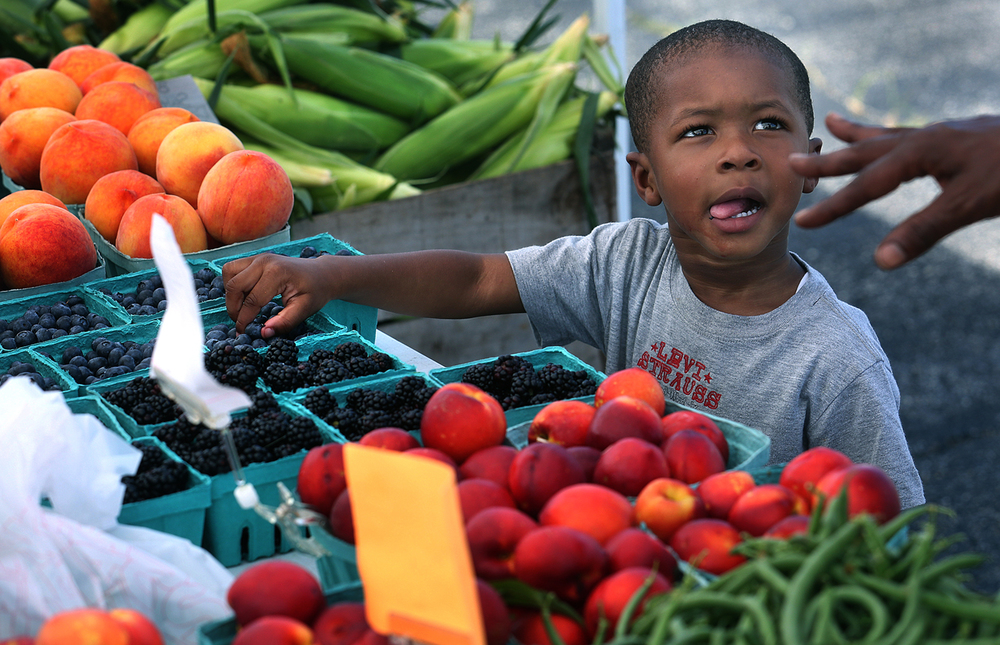 Major Rice, 2, of Springfield, looked to his great grandmother for permission to sample the blueberries at a table operated by Odelehr Farm at the East Side Famer's Market Monday, July 13, 2015. The market is held 2-6 p.m. on Mondays through Sept. 28 on the parking lot of the Sangamon County Department of Public Health, 2833 South Grand Ave. E. David Spencer/The State Journal-Register