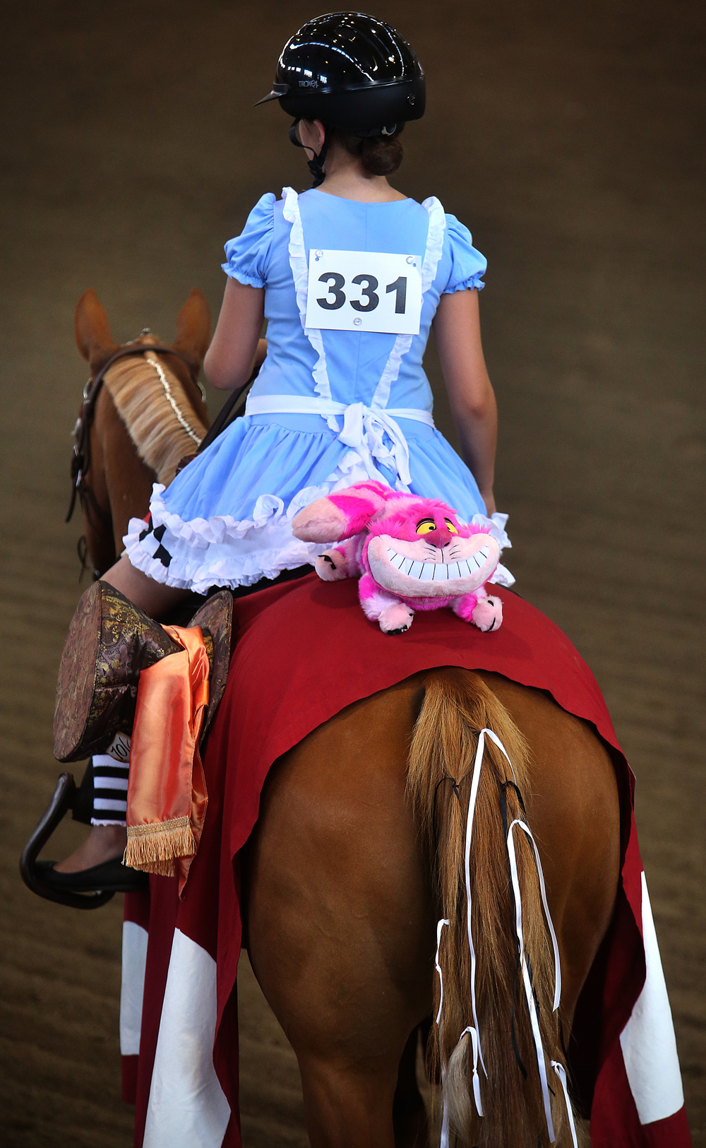 The Cheshire Cat of Alice in Wonderland fame holds on for dear life on the rear of horse Fantastic Royal Lady with Alice-aka Madisyn Hanson of Sangamon county-aboard. David Spencer/The State Journal-Register