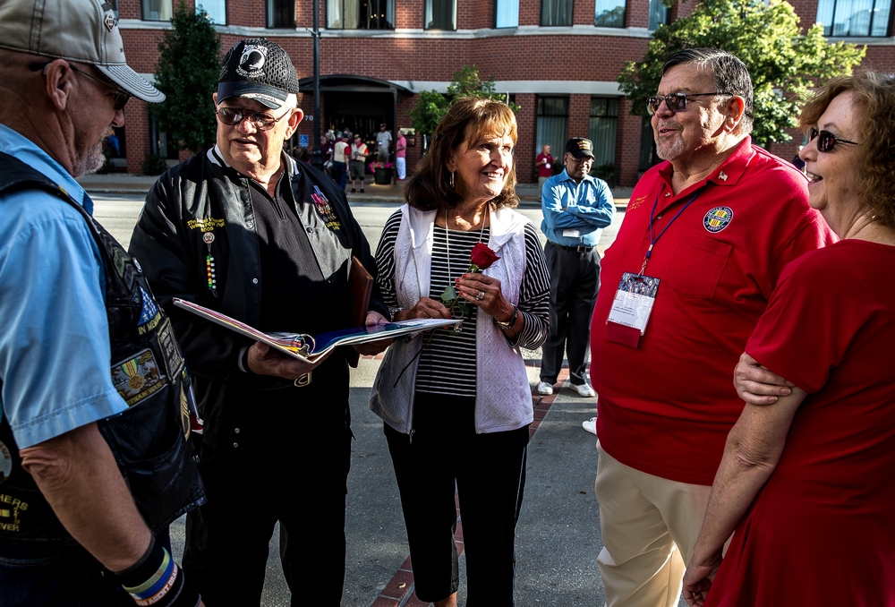 Pam Sigler, center, the wife of former Vietnam POW Gary Sigler, left, was given the rose from the Missing Man Table by former POW Bill Robinson, right, after the POW/MIA Ceremony during the Vietnam Veterans of America 2015 National Convention at the Hilton, Friday, July 24, 2015, in Springfield, Ill. Justin L. Fowler/The State Journal-Register