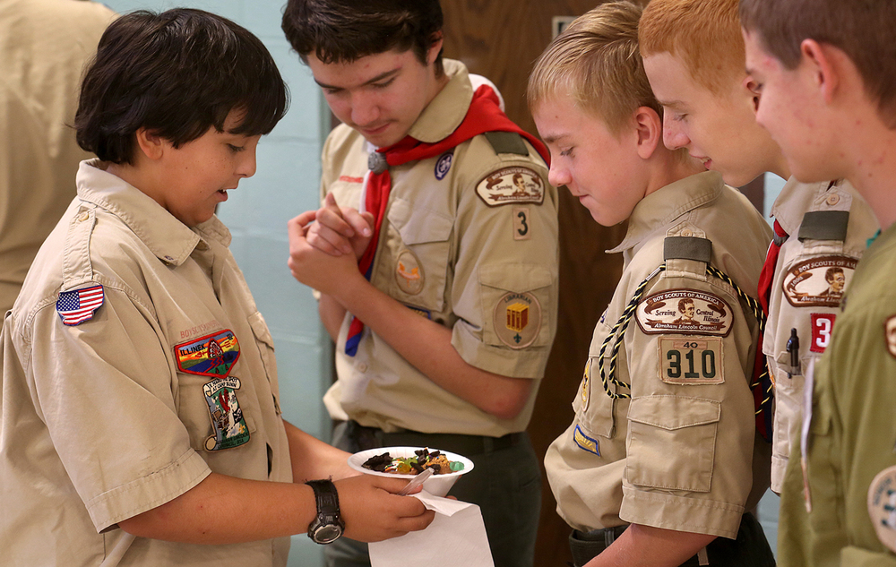 Marcus Pettus, 13, a member of Boy Scout Troop 3 at Douglas Avenue United Methodist Church, impresses his troop mates with his ice cream creation while they wait in line for their own Sunday, July 19, 2015. To celebrate the troop's 100th anniversary of its affiliation with the church,  it recreated an Ice Cream Social held there in 1915, as a thank you to the church community. David Spencer/The State Journal-Register