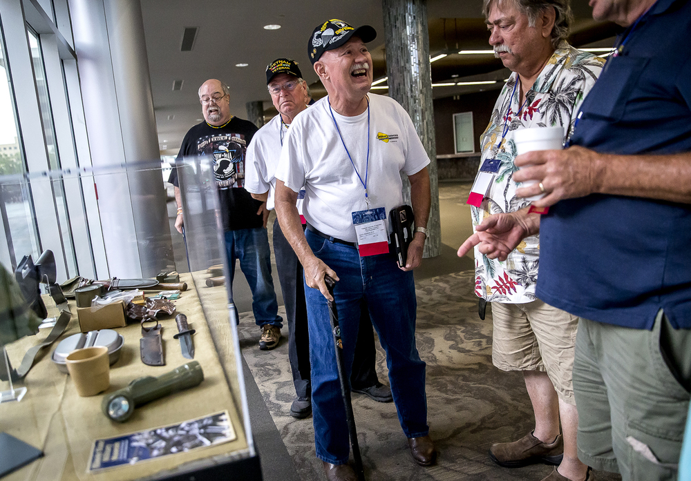 "Dr. David Brownfield, a delegate from VVA Chapter 810 of Chillicothe, Ohio, reminisces with fellow Vietnam veterans around an exhibit of military items on display during the Salute To America Veterans Concert presented by the Help Hospitalized Veterans for the Vietnam Veterans of America 2015 National Convention at Prairie Capital Convention Center, Tuesday, July 21, 2015, in Springfield, Ill.  ""The fellowship, I get to see every guy that went through the same thing I did,"" said Brownfield. ""You get to tell old stories that nobody understands."" Justin L. Fowler/The State Journal-Register More photos online at http://www.sj-r.com"