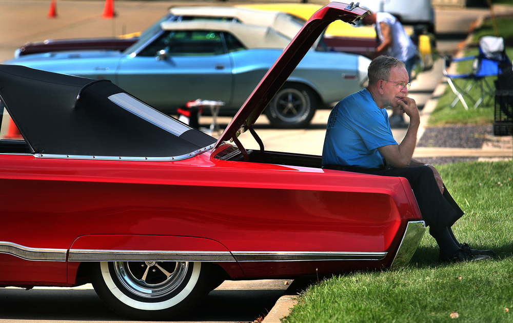 "Not only is Larry Hempel's 1967 Chrysler Newport Custom Convertible flashy, with a ""Scorch Red"" paint job, but the trunk lid serves as a handy way to stay out of the sun. Hempel was camped out in the parking lot of the hotel Thursday afternoon while taking part in a swap meet along with other car owners. Hempel said the car, which has been completely taken apart and restored, was purchased in New Jersey in the early 1990's. Brian The 46th Annual Walter P. Chrysler Restorers Club 