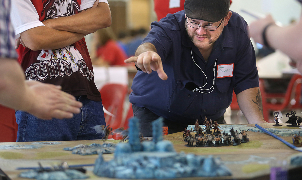 "Playing the skirmish tabletop fantasy game ""Warhammer: Age of Sigmar"", Springfield's Jason Deverick seemed intent on casting a spell on opponnent Bo Perkins, left, who prepares to roll multiple dice during game play Saturday morning. Capcon, a benefit for the Springfield High School World War II Memorial Scholarship Fund, took place in the school commons at the school on Saturday, July 25, 2015. Historical, fantasy, diehard and open gaming took place at the event. David Spencer/The State Journal-Register"
