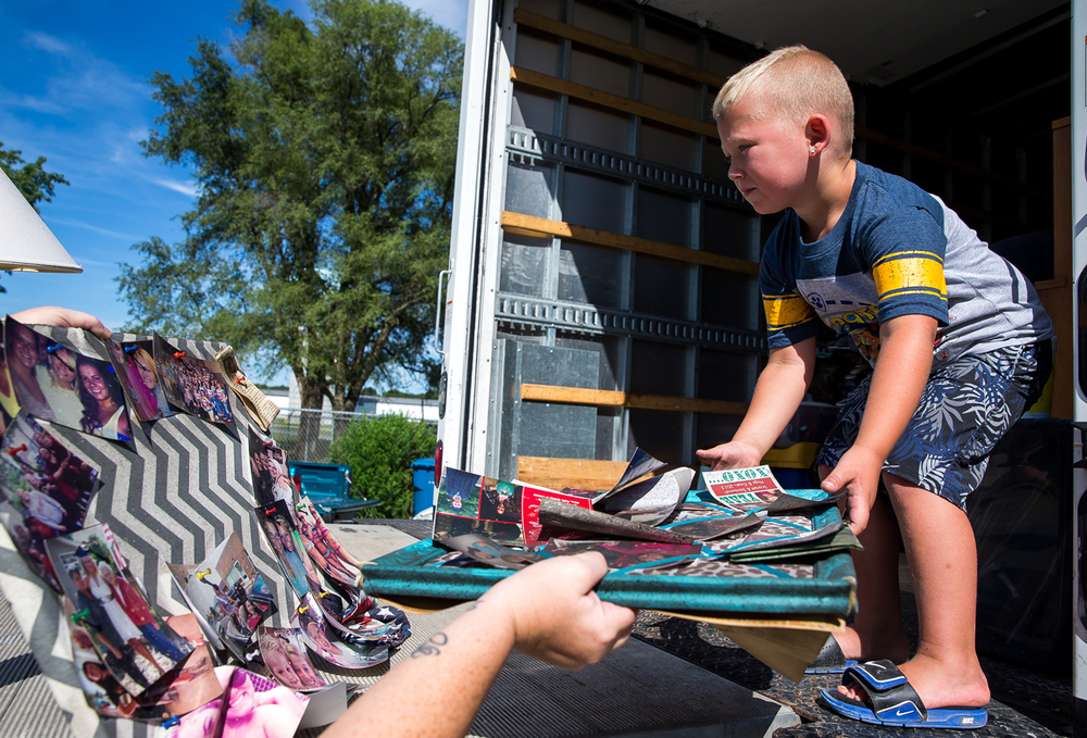 Finnegan Burke, 4, helps to load up picture boards into a truck as family and friends help salvage his families possessions the day after a fire destroyed their home, Wednesday, July 29, 2015, in Curran, Ill. Justin L. Fowler/The State Journal-Register