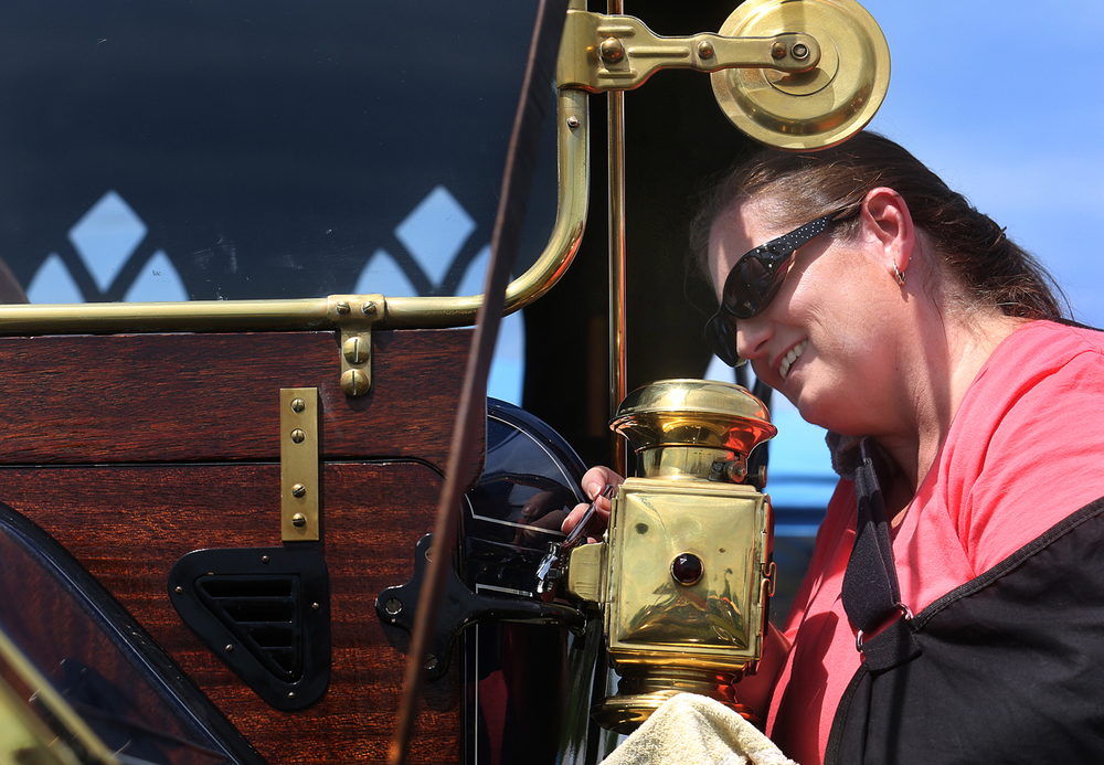 Tina Shobe of Urbana attaches brass coach lamps to a 1912 Maxwell Mascotte that is owned by her brother, Troy Todd, at the third annual Powerlight Abe Lincoln Car Show Spectacular Saturday, Aug. 1, 2015 at Knight's Action Park. The Indiana-built automobile features right-hand steering and has been in the family since 1971 when Shobe's grandfather purchased the automobile. David Spencer/The State Journal-Register