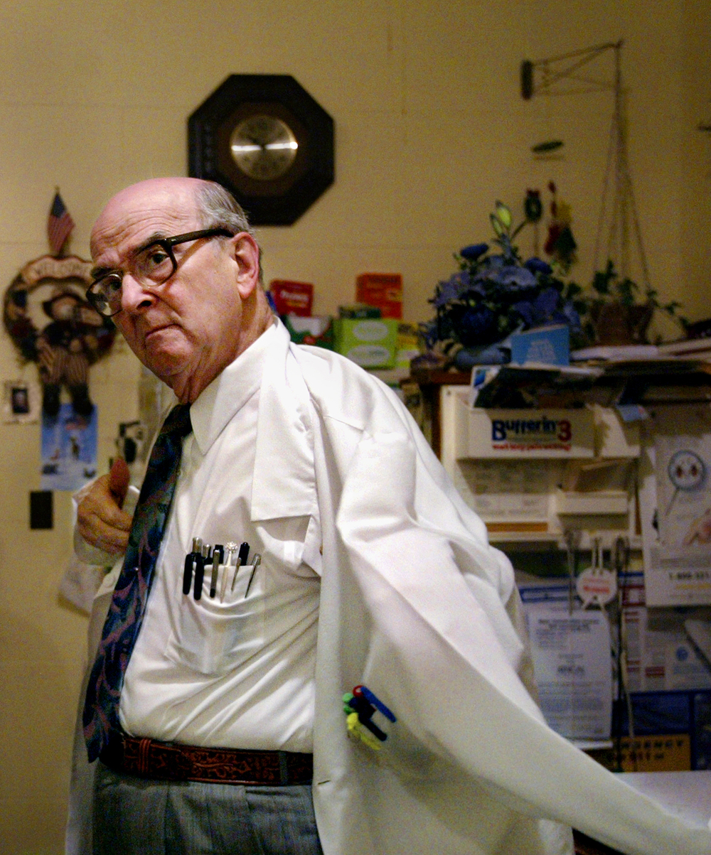 """Dr. Russell Dohner, 79, slips on his lab coat at his private office located on the square in Rushville after making rounds at the Sarah D. Culbertson Memorial Hospital. Dohner has always dreamt of seeing the Rocky Mountains, but never takes vacations. """"Not until my work is done,"""" Dohner said. Photo by Shannon Kirshner/The State Journal-Register"""