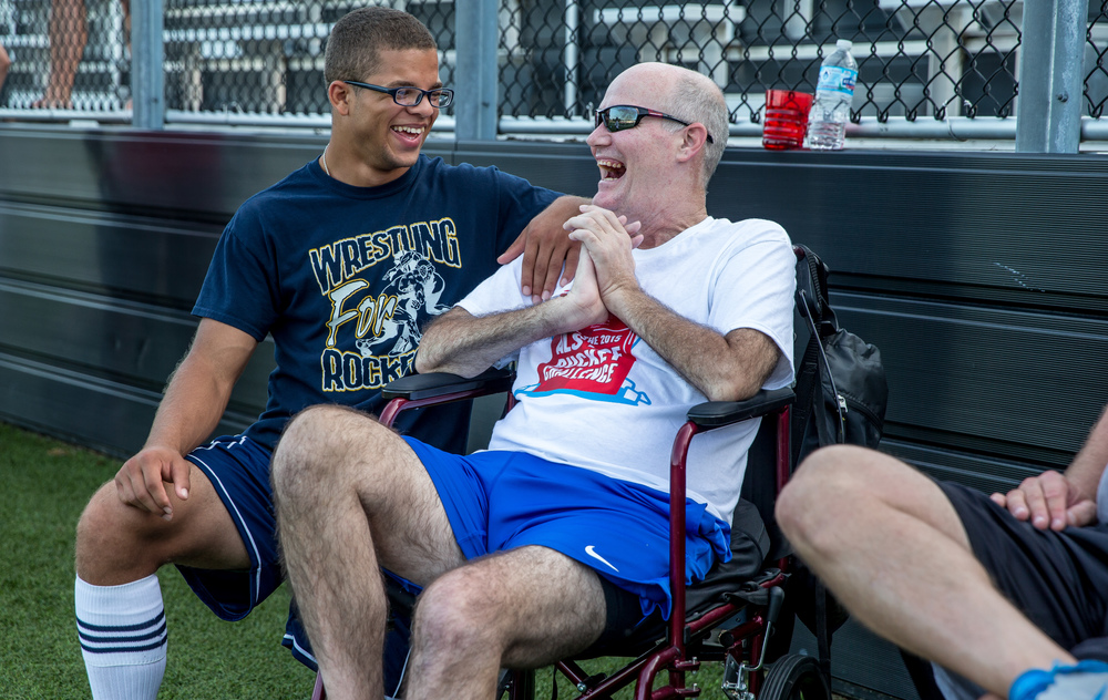 "Isiah Cotton, a graduate of Southeast High School, left, visits with Steve Rockford along the sidelines before a mass ALS Ice Bucket Challenge at the Sacred Heart-Griffin Sports Complex, Friday, Aug. 7, 2015, in Springfield, Ill.  ""To remember that he is a fighter and he's taught us to be fighters throughout our lives and to live life the best way that we can everyday,"" said Cotton of participating in the event. Justin L. Fowler/The State Journal-Register"