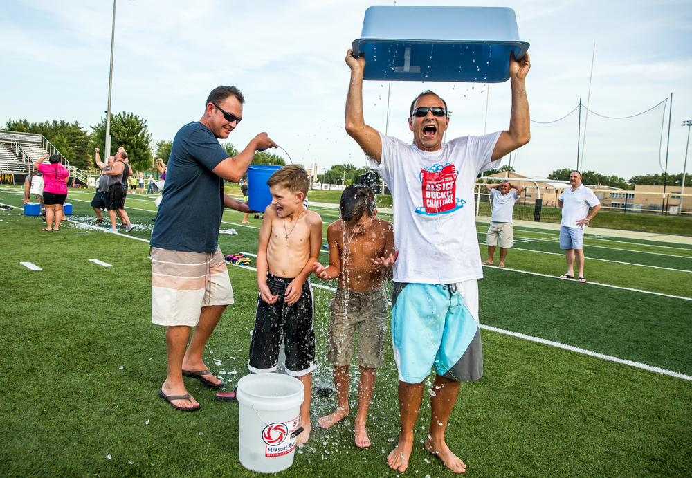 Levent Ozyurt, right, dumps a bin of a ice water on himself and his son, Berk, as Nick Faulkner, left, prepares to douse his son, Harrison, during a mass ALS Ice Bucket Challenge at the Sacred Heart-Griffin Sports Complex, Friday, Aug. 7, 2015, in Springfield, Ill. Justin L. Fowler/The State Journal-Register