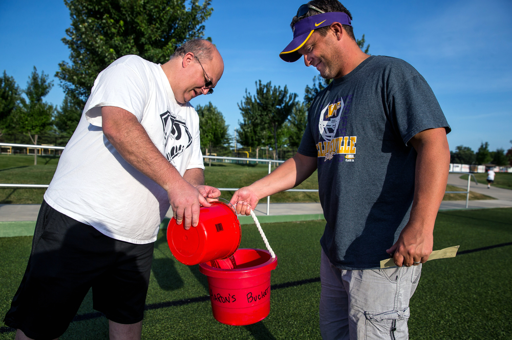 Jason Mitchell, left, helps Williamsville football coach Aaron Kunz, load up his bucket of ice with water for the ALS Ice Bucket Challenge at the Sacred Heart-Griffin Sports Complex, Friday, Aug. 7, 2015, in Springfield, Ill. Justin L. Fowler/The State Journal-Register