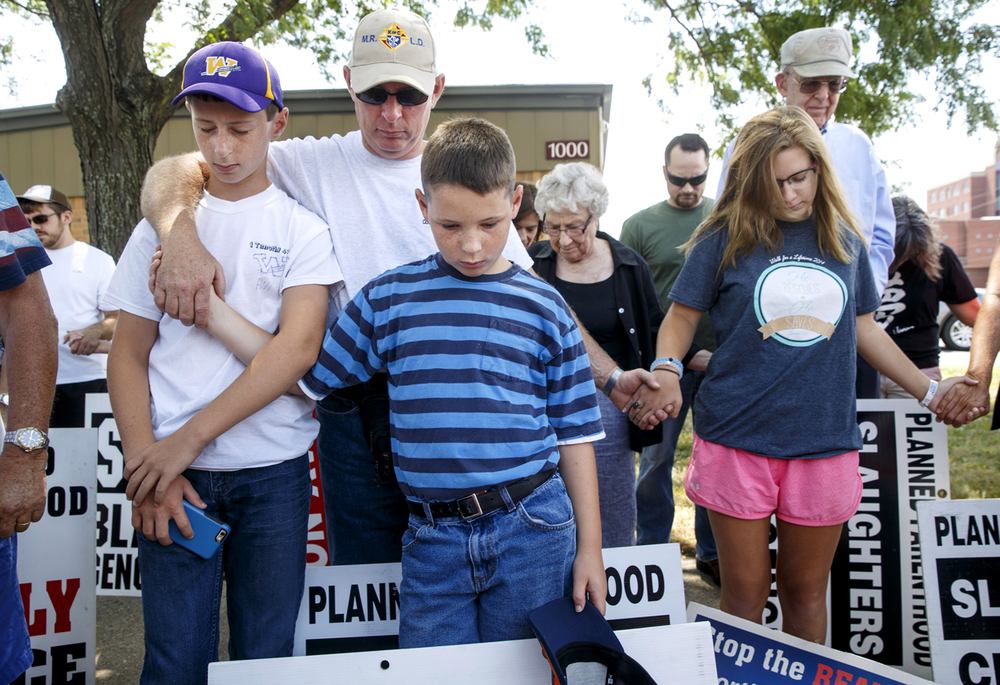 Keith Spaniol and his sons Bill, left, and Kenny bow in prayer with about 80 others during a pro-life rally in front of Planned Parenthood's Springfield health center Thursday, Aug. 6, 2015. Ted Schurter/The State Journal-Register