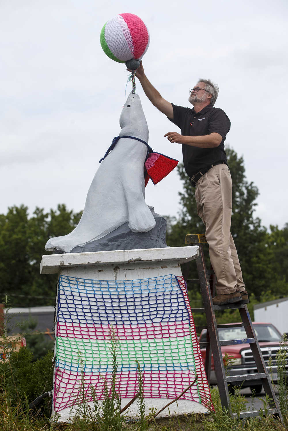 Ace Sign Co. president Dennis Bringuet repositions a beach ball with a knitted cover on top of the Bel-Aire Motel seal on the company's property Wednesday, Aug. 5, 2015. The company moved the 8,000-pound concrete seal after mayor Jim Langfelder purchased it and after a group of knitters decorated it in yarn. Ted Schurter/The State Journal-Register