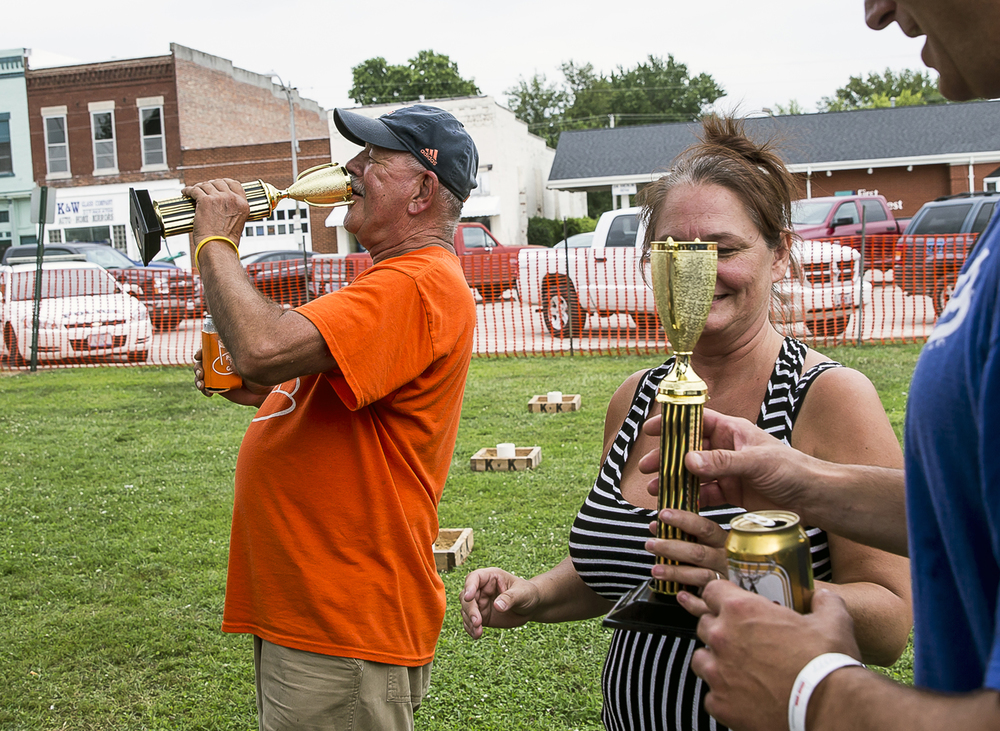 Rick Codron, left, pretends to drink from a trophy after he and John Kollins, right, won a round of the washers tournament at the Virden Picnic on the square, Saturday, Aug. 8, 2015, in Virden, Ill. Justin L. Fowler/The State Journal-Register