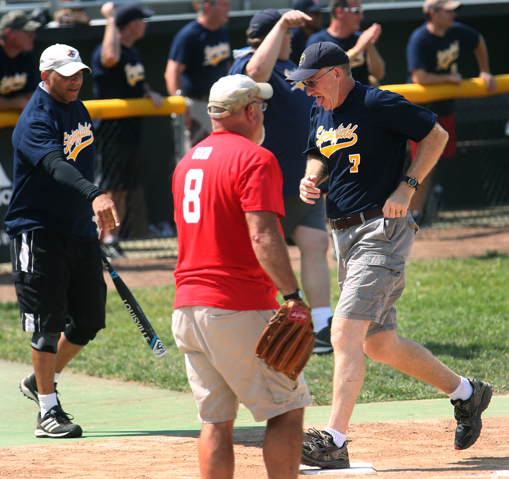Springfield alderman Herman Senor at left points to the bag as fellow alderman Joe McMenamin steps on home plate for a run. Sangamon county elected officials defeated Springfield City officials 11-10 in the fourth annual softball game at Robin Roberts Stadium in Springfield on Sunday, August 2, 2015. David Spencer/The State Journal-Register