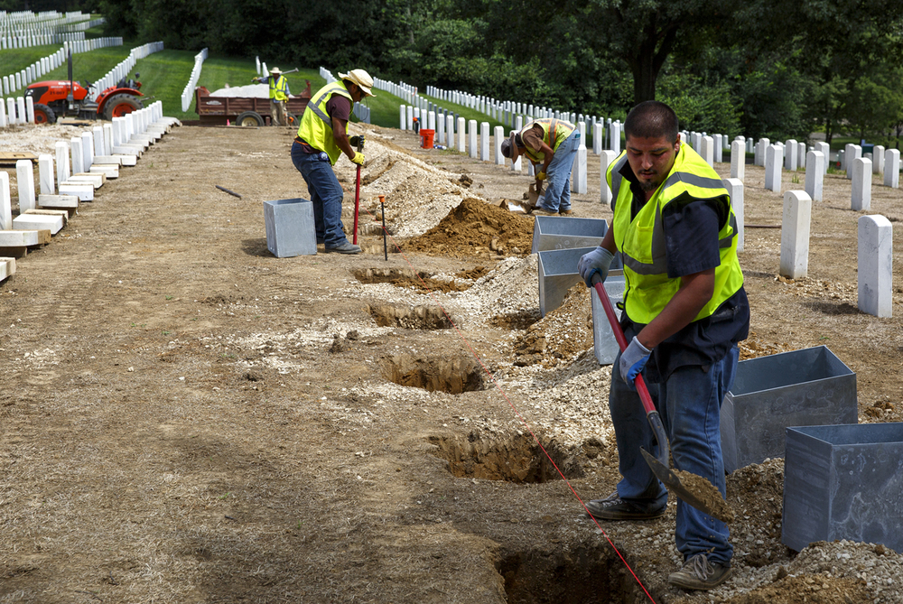 Amador Rojas, right, and other employees of Team West Contracting Corporation, install metal boxes that stabilize and anchor the headstones at Camp Butler National Cemetery Monday, Aug. 3, 2015. Headstones in certain areas of the cemetery are being removed and reset with the improved system as part of ongoing upgrades, which also includes the installation of an irrigation system. Rich Saal/The State Journal-Register