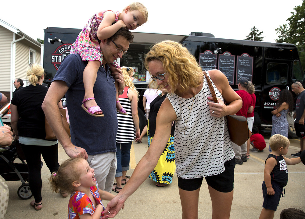 "Simon and Jennifer Bekker and their 3-yeard-old twin daughters, Ilana, top and Naomi, waited in a lengthy line for dinner from Cooper's strEATside Bistro at ""Bites on the Boulevard,"" a pop-up gathering of food trucks in a lot at 1413 S. MacArthur Tuesday, Aug. 4, 2015. Four food trucks participated and a large turnout kept the lines long throughout the three-hour event. Rich Saal/The State Journal-Register"