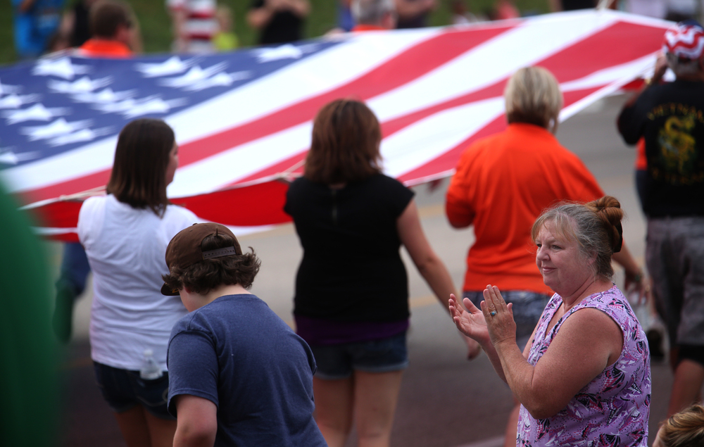 A woman claps as a large American flag carried by members of Elks Lodge 158 passes by on the parade route. David Spencer/The State Journal-Register