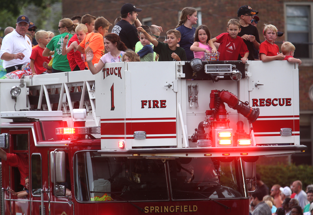 Children throw candy while standing atop a Springfield Fire Department aerial truck along the parade route. David Spencer/The State Journal-Register