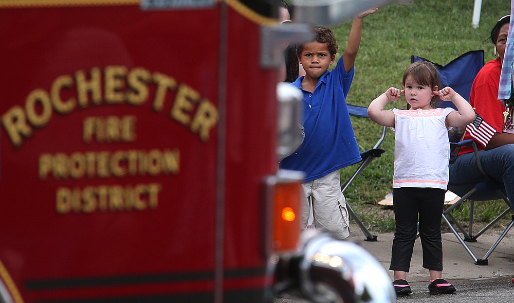 Children wave and protect their ears as a Rochester Fire Department truck passes along the parade route. David Spencer/The State Journal-Register
