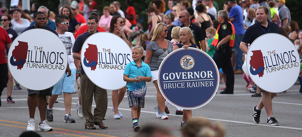 Circular placards advertising Ill Gov. Bruce Rauner's Turnaround agenda were carried along the parade route while the Governor walked nearby. David Spencer/The State Journal-Register