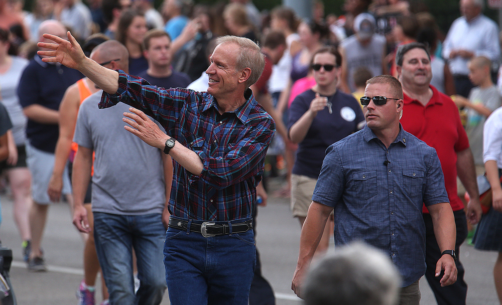 Illinois Gov. Bruce Rauner waves while walking along the parade route.David Spencer/The State Journal-Register