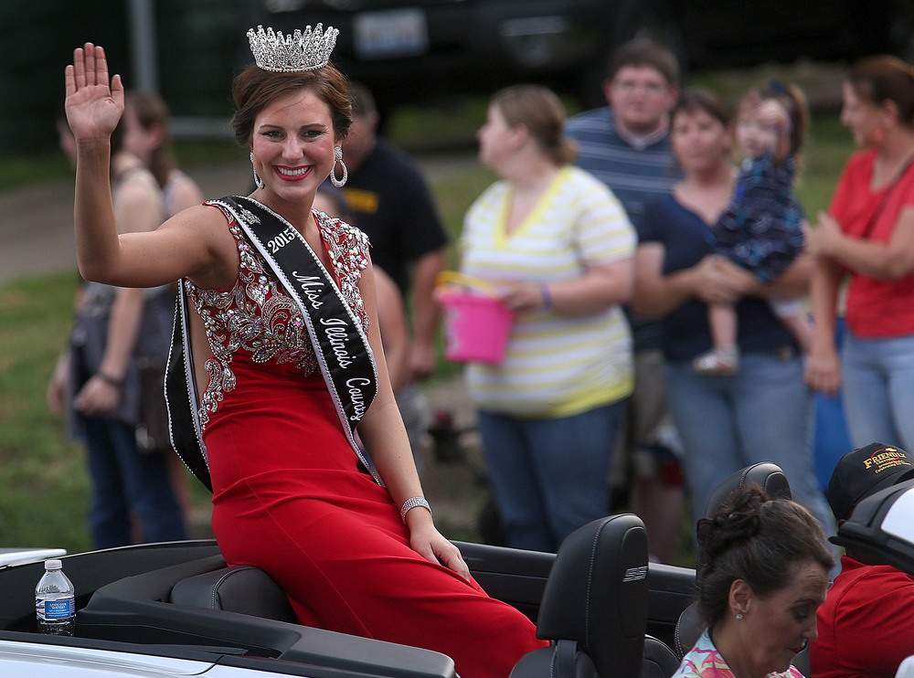 2015 Illinois County Fair Queen Saadie Gassmann waves while riding along the parade route. David Spencer/The State Journal-Register
