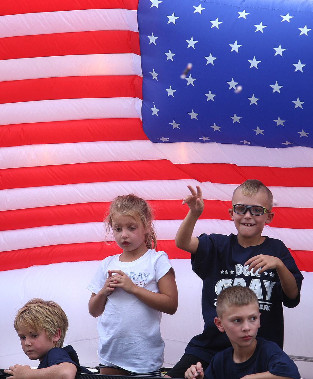 Children throw candy from a float having the backdrop of an inflatable American flag along the parade route.  David Spencer/The State Journal-Register