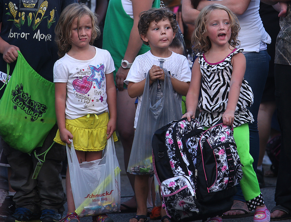 Children hold their candy bags along the side of the parade route. David Spencer/The State Journal-Register