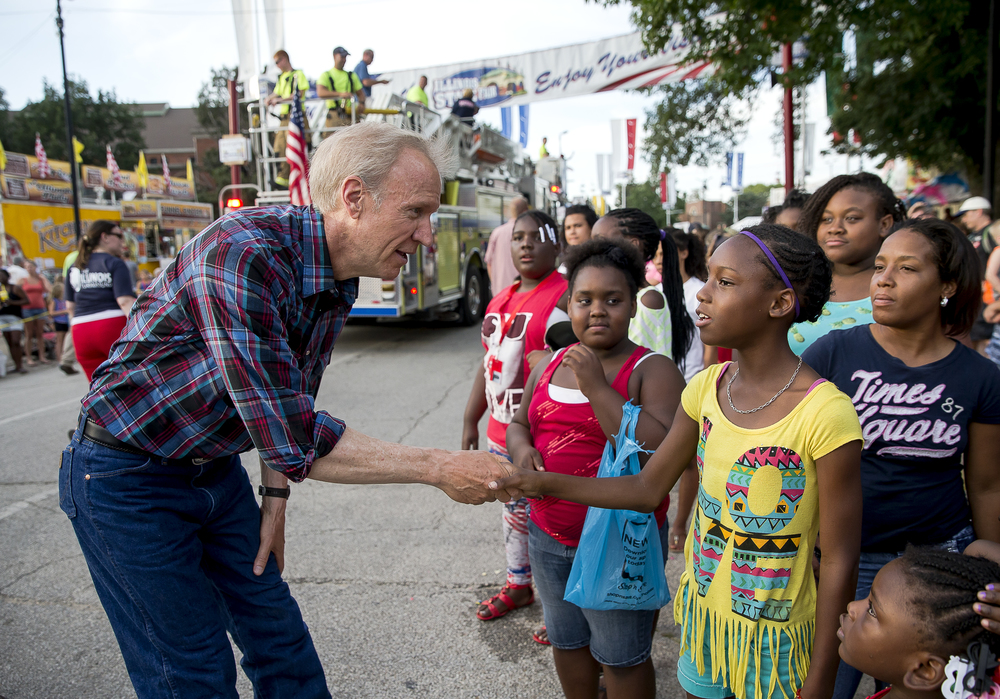 Illinois Gov. Bruce Rauner shakes hands with Monique Hayes, 11, as he makes his way up Main Street during the 2015 Illinois State Fair Twilight Parade at the Illinois State Fairgrounds, Thursday, Aug. 13, 2015, in Springfield, Ill. Justin L. Fowler/The State Journal-Register