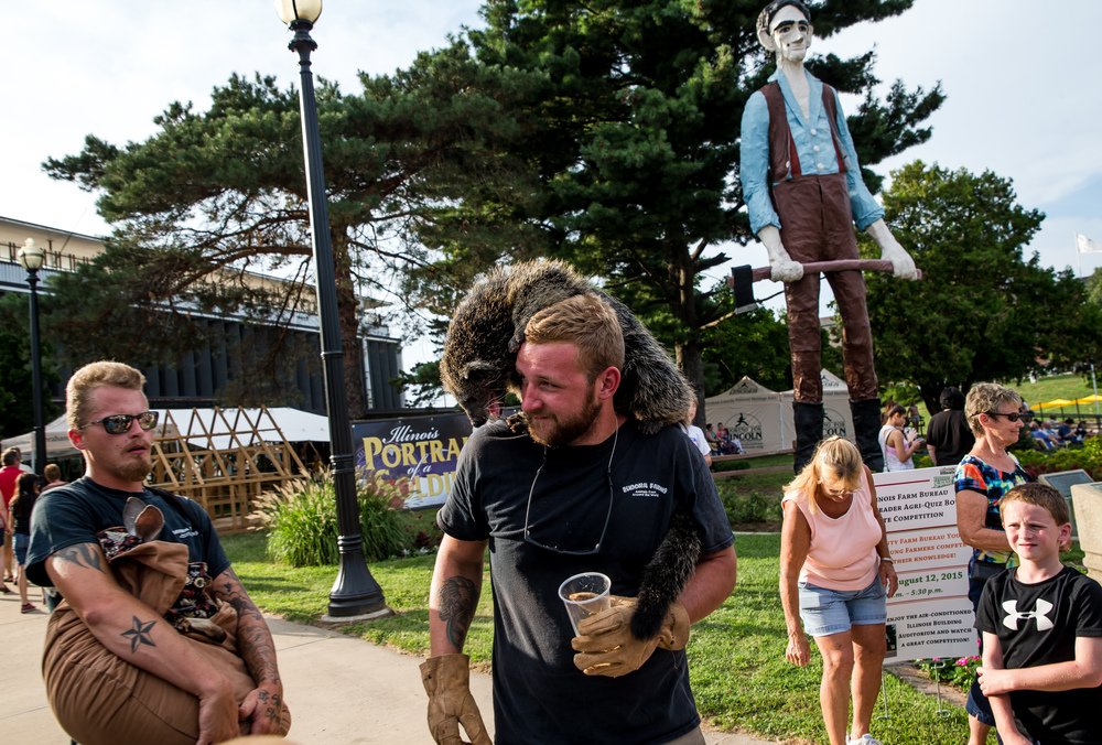 Cody Duncan keeps a bearcat happy atop his shoulders as he prepares for an interview about the Eudora Farms exhibit in Happy Hollow during the 2015 Illinois State Fair Twilight Parade at the Illinois State Fairgrounds, Thursday, Aug. 13, 2015, in Springfield, Ill. Justin L. Fowler/The State Journal-Register
