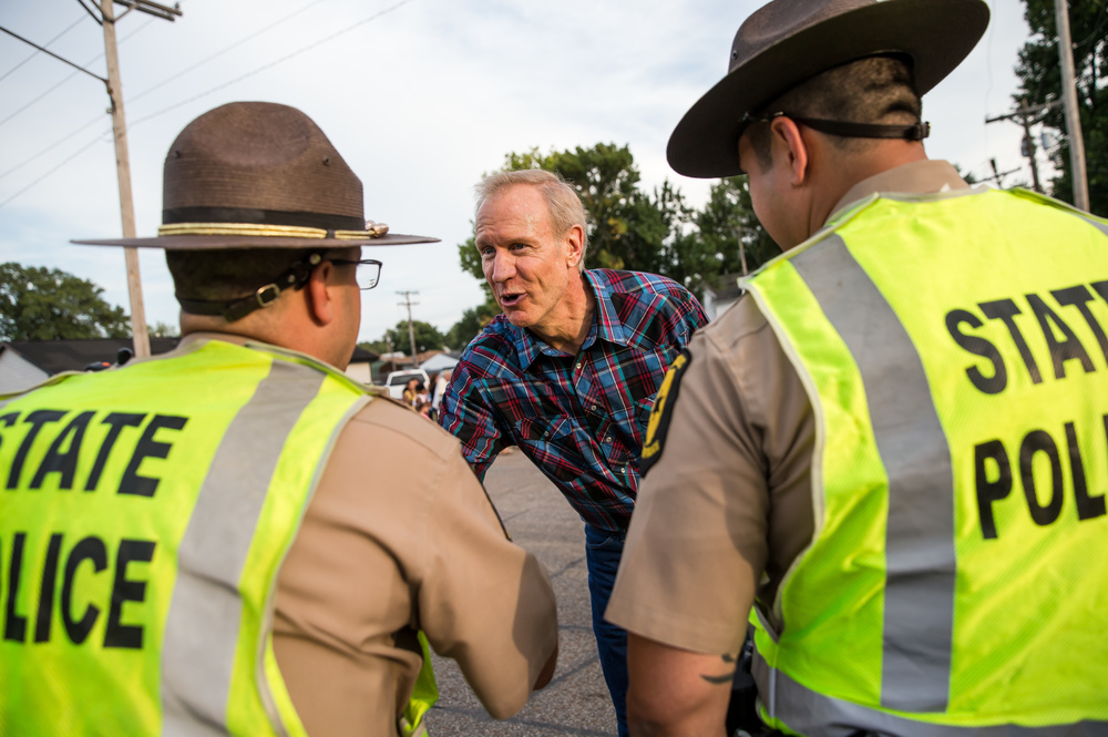 Illinois Gov. Bruce Rauner shakes hands with officers from the Illinois State Police during the 2015 Illinois State Fair Twilight Parade at the Illinois State Fairgrounds, Thursday, Aug. 13, 2015, in Springfield, Ill. Justin L. Fowler/The State Journal-Register