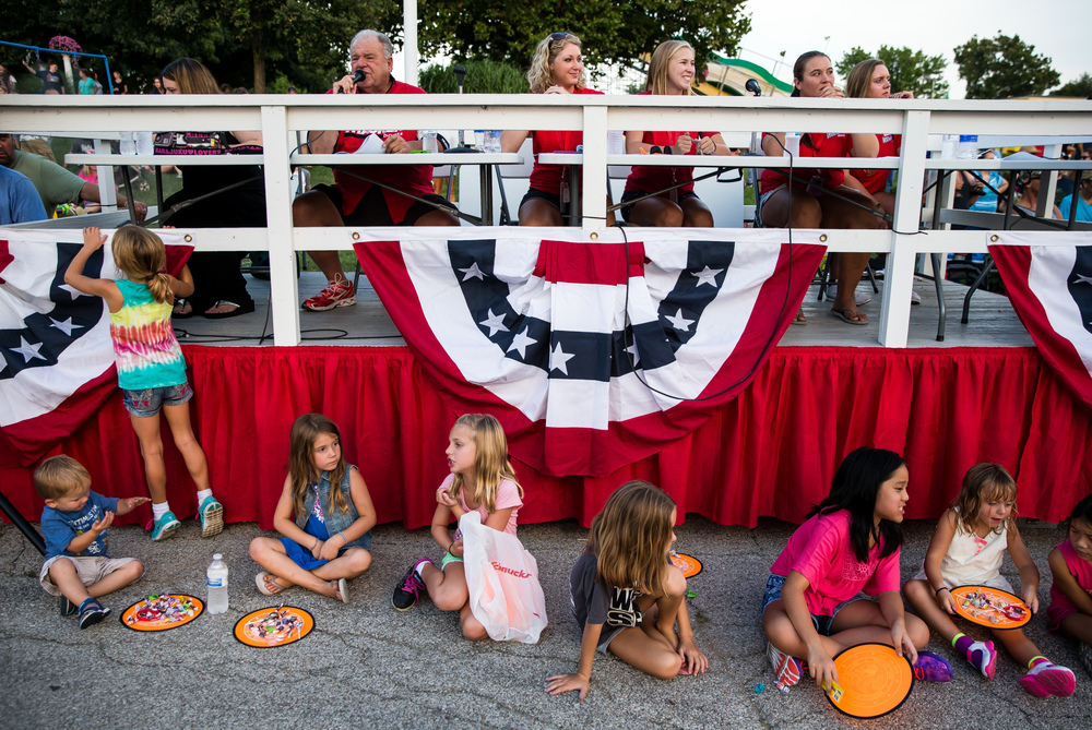 Children line up for candy in front the announcers table as Sam Madonia calls out the floats during the 2015 Illinois State Fair Twilight Parade at the Illinois State Fairgrounds, Thursday, Aug. 13, 2015, in Springfield, Ill. Justin L. Fowler/The State Journal-Register